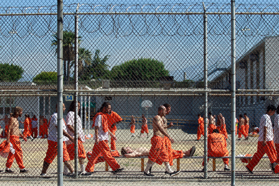 """Inmates walk around an exercise yard at the California Institution for Men state prison in Chino, California, June 3, 2011. The Supreme Court has ordered California to release more than 30,000 inmates over the next two years or take other steps to ease overcrowding in its prisons to prevent """"needless suffering and death."""" California's 33 adult prisons were designed to hold about 80,000 inmates and now have about 145,000. The U.S. has more than 2 million people in state and local prisons. It has long had the highest incarceration rate in the world. REUTERS/Lucy Nicholson (UNITED STATES - Tags: CRIME LAW POLITICS SOCIETY) - RTR2N9TX"""
