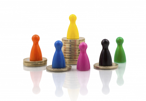 Colorful figures on different coin stacks. Concept for wealth difference.